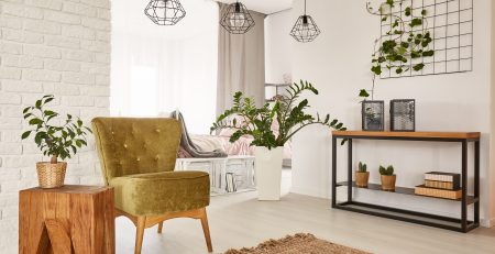 White room with green armchair and wooden side table